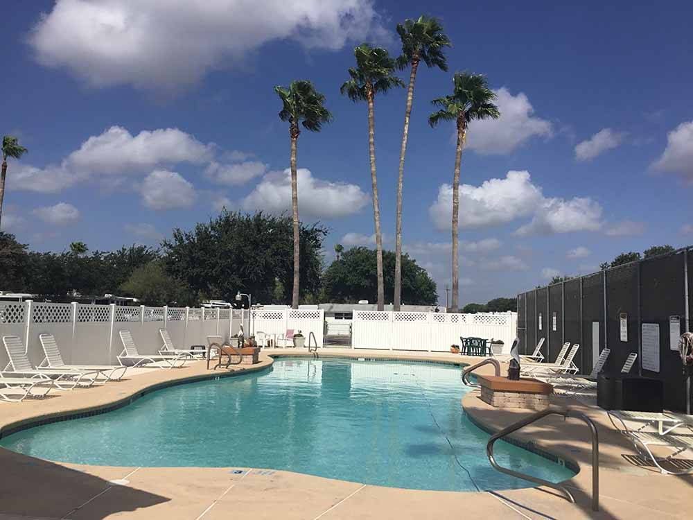 A view of the pool with lounge chairs at TEXAS TRAILS RV RESORT