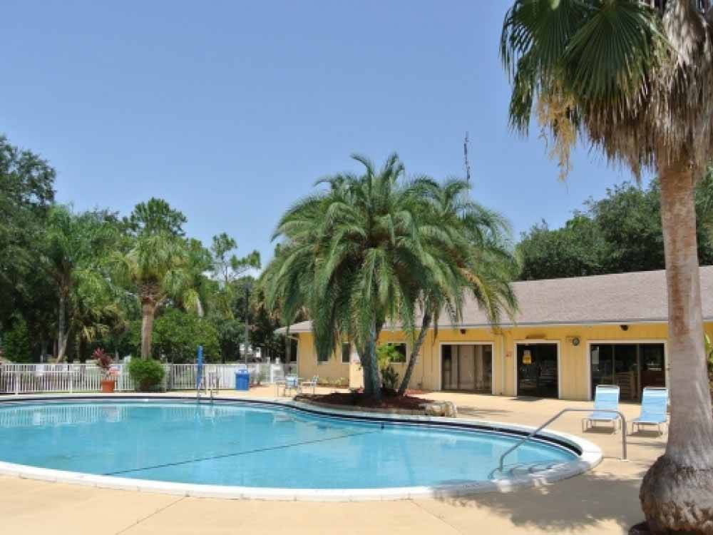 Swimming pool with outdoor seating at SUNSHINE TRAVEL RV RESORT