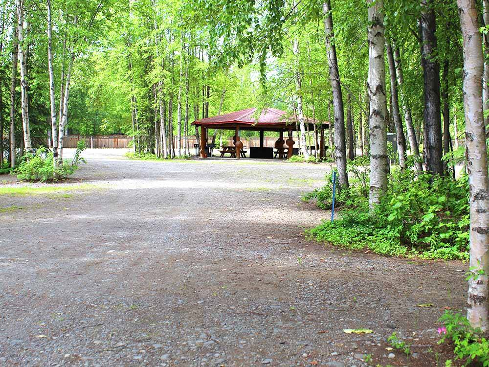 A gravel road leading to a pavilion at TRAPPER CREEK INN  RV PARK