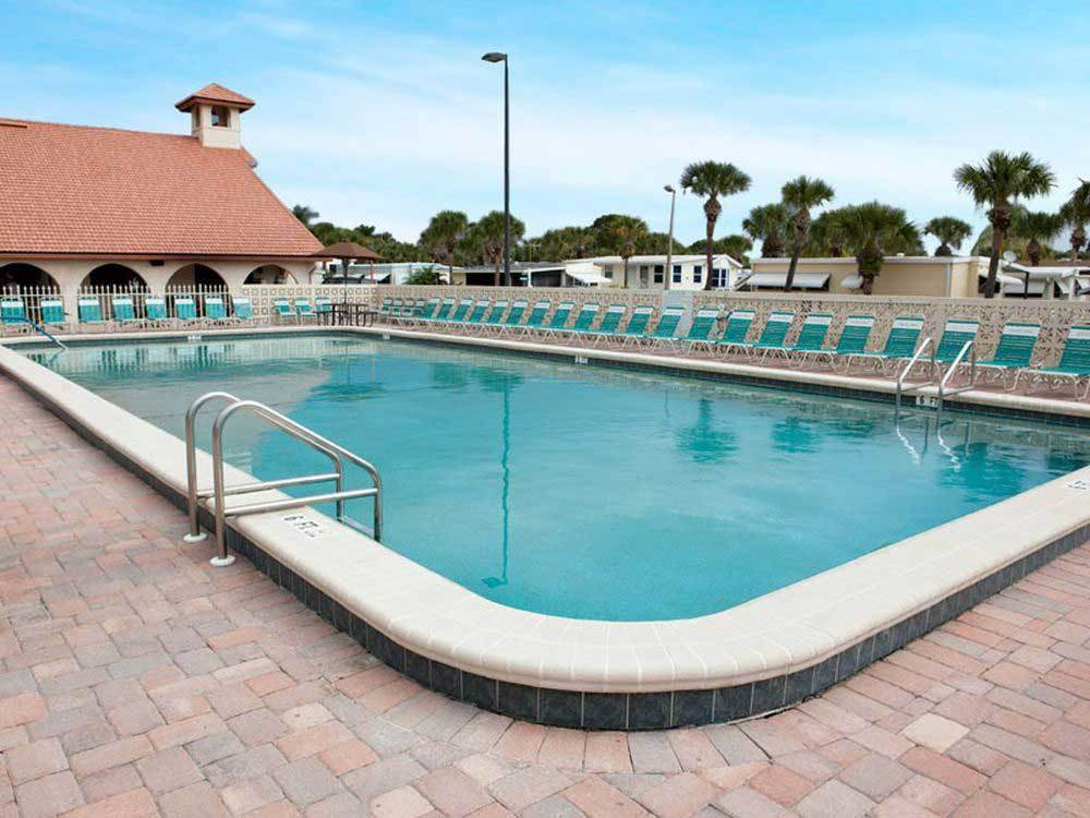 Swimming pool with outdoor seating at SIESTA BAY RV RESORT