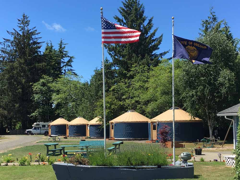 Row of yurts behind a grass area with seating at TILLAMOOK BAY CITY RV PARK
