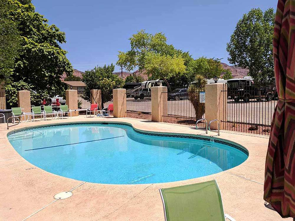 Large bean shaped community pool with green lounge chairs around it at KANAB RV CORRAL