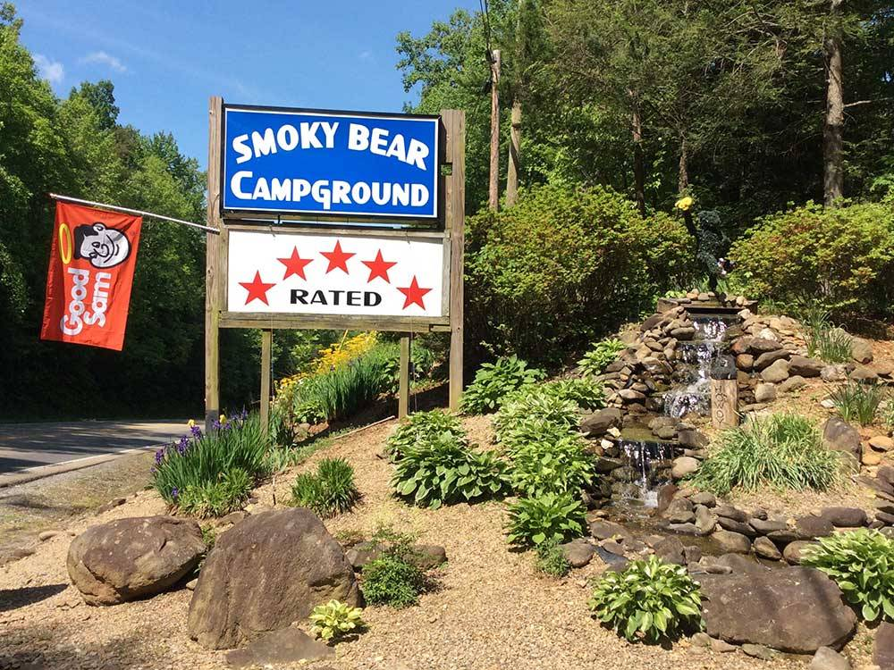 Park sign at entrance with small waterfall feature at SMOKY BEAR CAMPGROUND AND RV PARK