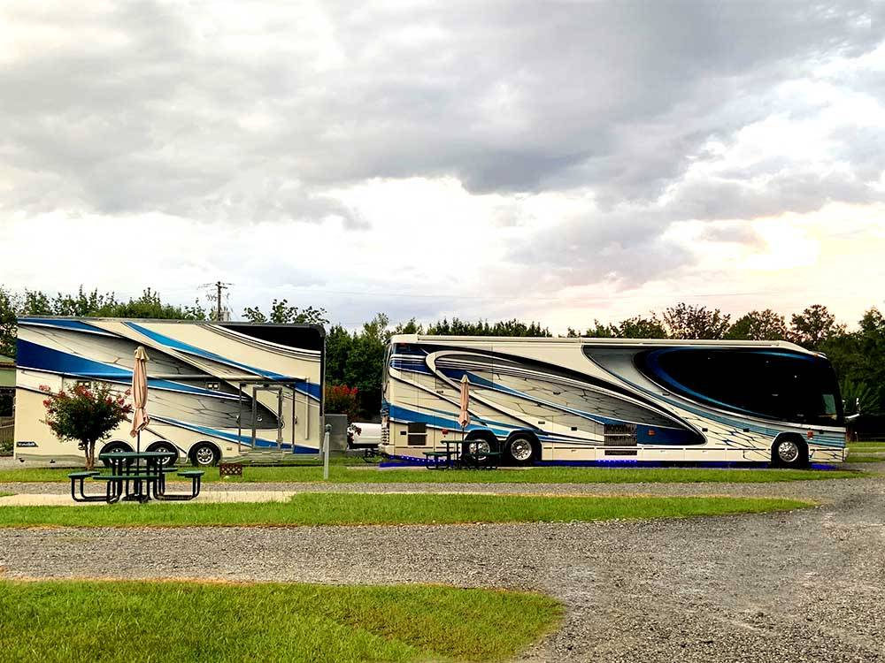 Two big rigs parked in gravel sites  at TWIN OAKS RV PARK