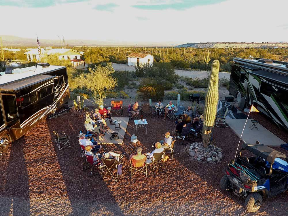 Campers seated in a circle between RVs at AJO HEIGHTS RV PARK