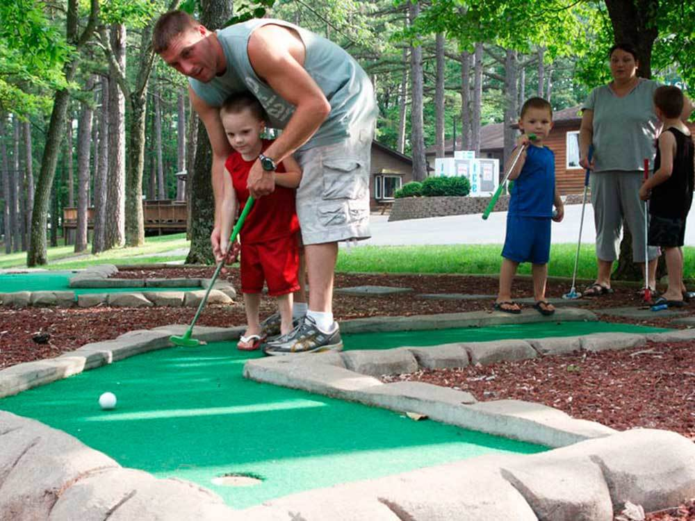 Man and young boy playing mini golf at LAKE RUDOLPH CAMPGROUND  RV RESORT