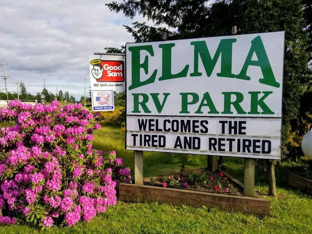 Park sign next to pink flowers and Good Sam sign at ELMA RV PARK