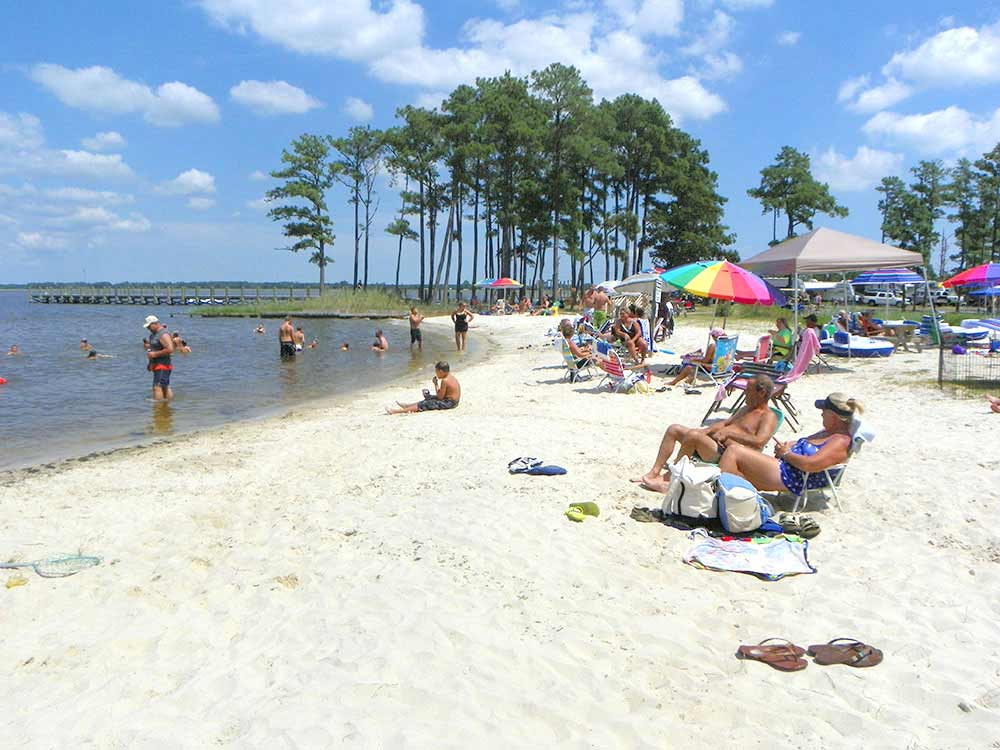 Campers enjoying the beach at TALL PINES HARBOR WATERFRONT CAMPGROUND