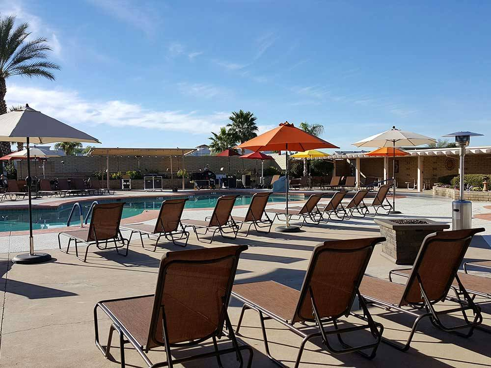 Swimming pool with outdoor seating and orange umbrellas at FAR HORIZONS RV RESORT