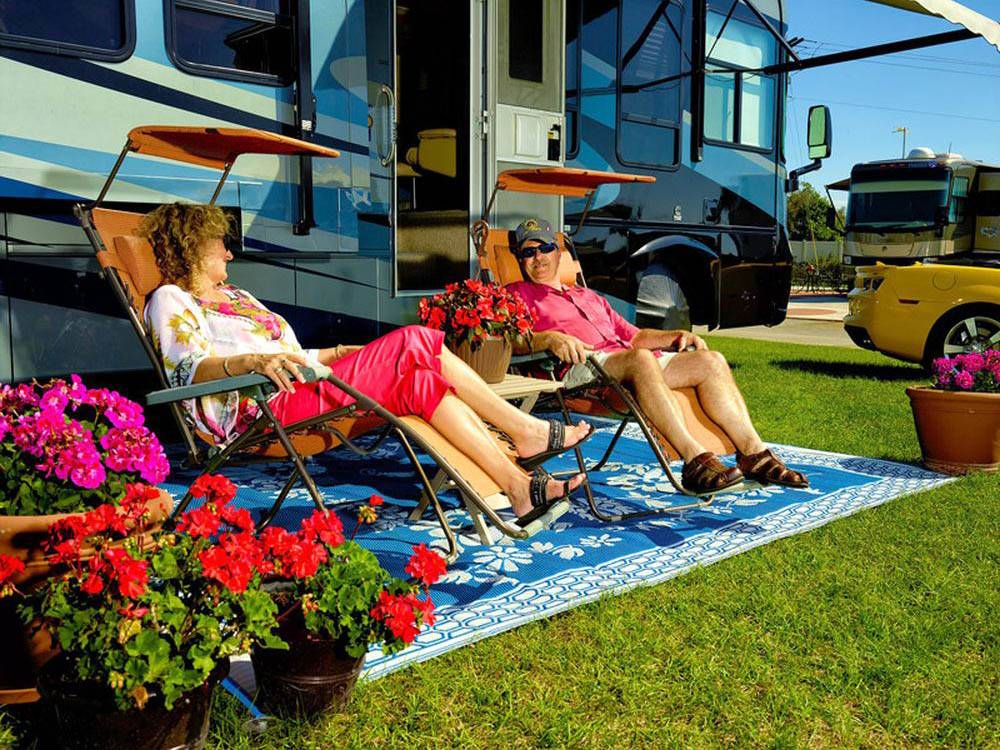 Couple camping in RV at WHISPER CREEK RV RESORT