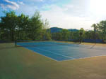 View larger image of Empty tennis court with sun reflecting subtly off of it at CAMP RIVERSLANDING image #5