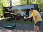 View larger image of Man playing a game of cornhole beside trailer at CAMP RIVERSLANDING image #10
