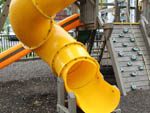 View larger image of Bright yellow winding slide at playground at CAMP RIVERSLANDING image #12