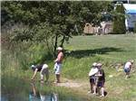 View larger image of Family sitting at picnic table at MAPLE LAKES RECREATIONAL PARK image #5