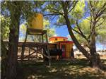 View larger image of A yellow caboose sitting next to a tree at OASIS RV RESORT  COTTAGES - DURANGO image #9