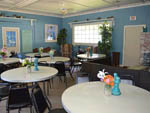 View larger image of Tables and black chairs in dining room with blue wallpaper at RIVERDALE FARM CAMPSITES image #8