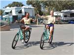 View larger image of A couple of girls holding hands riding bikes at CAMPLAND ON THE BAY image #3