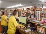 View larger image of Young family talking to staff workers in the convenience store at SALT LAKE CITY KOA image #3