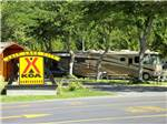 View larger image of Yellow campground entrance sign with large tan RV in background at SALT LAKE CITY KOA image #9