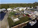 View larger image of Aerial view of mobile home park with palm trees and American flag at UPRIVER RV RESORT image #5