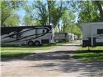 View larger image of RVs and truck and trailers camping among green trees at HAPPY HOLIDAY RESORT image #4