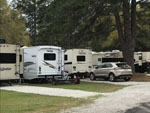 View larger image of White and tan travel trailers camping at campsite at WHISPERING PINES RV PARK image #3
