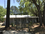 View larger image of Rocking bench and lodge at WHISPERING PINES RV PARK image #8