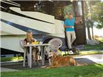 View larger image of A dog sitting in front of a woman with a man holding a cup exiting a Class A RV at LAKESIDE CASINO  RV PARK image #11