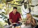 View larger image of A woman holding a drink as a man serves her food at LAKESIDE CASINO  RV PARK image #12