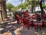 View larger image of A group of red chairs sitting around a fire pit at BLACK CANYON RANCH RV RESORT image #3