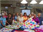 View larger image of A group of women holding up a quilt at BLACK CANYON RANCH RV RESORT image #8