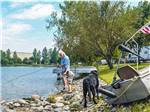 View larger image of A man fishing with a black dog looking on at CABOOSE LAKE CAMPGROUND image #12