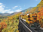 View larger image of A train going over a bridge in the fall at WHITE MOUNTAINS ATTRACTIONS ASSOC image #3