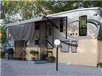 View larger image of Gray trailer setup in semi-permanent fashion on gravel spot at CORONADO VILLAGE RV RESORT image #4