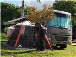 View larger image of RV with tent pitched up next to it at BOARDWALK RV RESORT image #10
