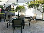 View larger image of Multiple patio table and chair sets on sand gravel surface at PALM BEACH TRAVELER RV PARK image #2