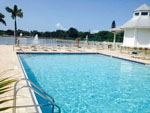View larger image of Swimming pool with outdoor seating at GULF WATERS RV RESORT image #4