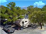 View larger image of Trailer in a gravel site with pine trees at PREFERRED RV RESORT image #2