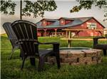 View larger image of Lawn with fire pit and chairs at RUSTIC MEADOWS RV PARK image #3