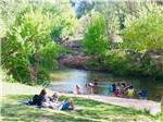 View larger image of People relaxing by the river at RIO VERDE RV PARK image #3