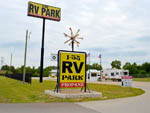 View larger image of Bright yellow entrance sign with black lettering at I 35 RV PARK  RESORT image #5