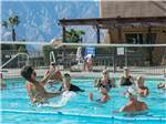 View larger image of Large group of campers playing volleyball in community pool at CATALINA SPA AND RV RESORT image #8