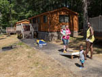 View larger image of People playing cornhole by a cabin at WILDERNESS PRESIDENTIAL RESORT image #5