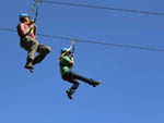 View larger image of A man and woman zip lining at FALLS CREEK CABINS  CAMPGROUND image #2