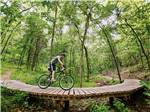 View larger image of A man on a bike on a wooden bridge at BLOWING SPRINGS RV PARK image #5
