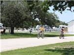 View larger image of Two people riding their bikes on one of the roads at VICTORIA COLETO LAKE RV RESORT image #3
