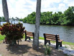 View larger image of Wooden benches looking out onto flowing river at ORANGE HARBOR CO-OP  RV RESORT image #1