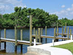 View larger image of Three thin boat docks in a row along calm river at ORANGE HARBOR CO-OP  RV RESORT image #5