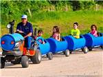 View larger image of Man on tractor towing kids at ASHAWAY RV RESORT image #7