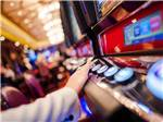 View larger image of A person pressing the buttons on a slot machine at THE RV PARK AT ROLLING HILLS CASINO AND RESORT image #4